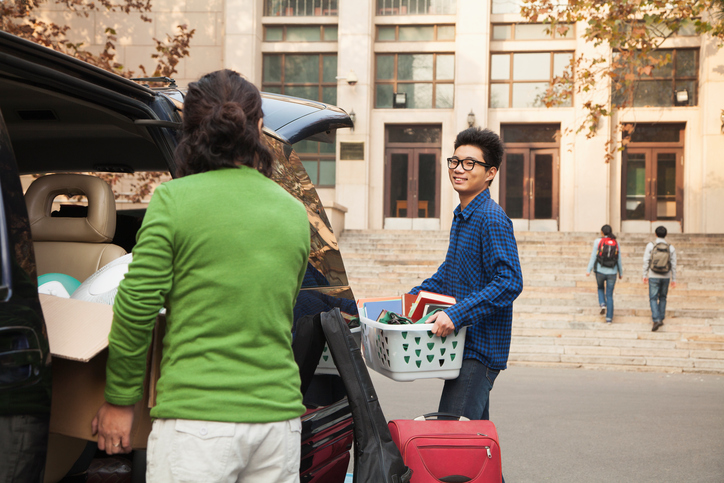 A young man moving into a residence hall.